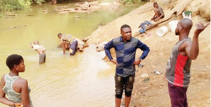 Despite COVID-19, Enugu community sources water from filthy river